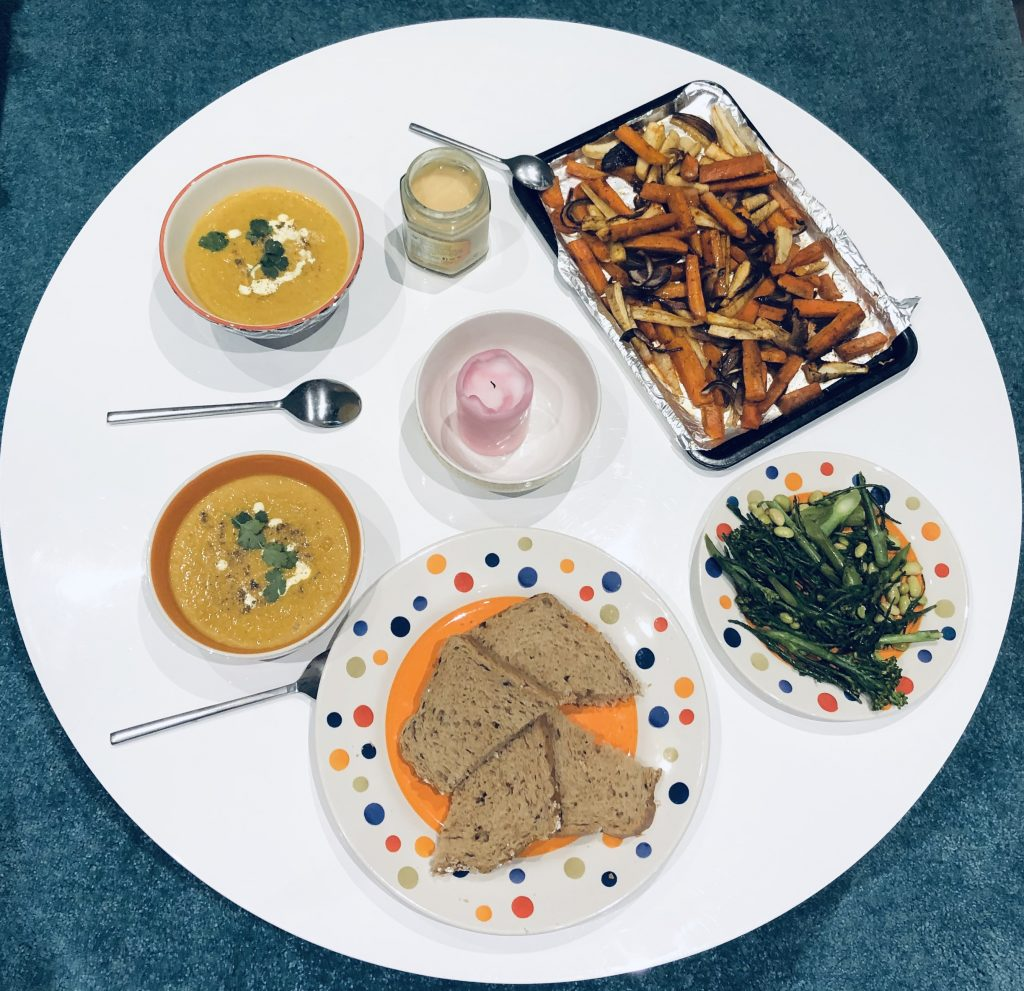 Top down image of the final meal, featuring two bowls of soup, bread, the roasted vegetables, and cooked greens.