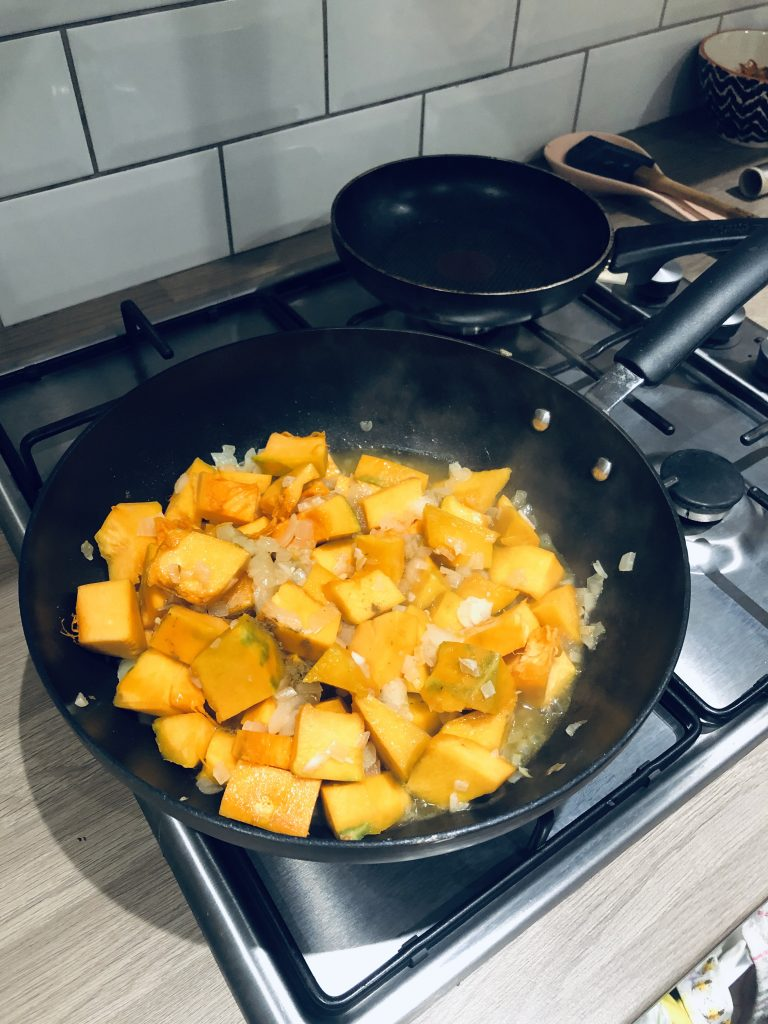 Top down image of a pan with the pumpkin cooking in a wok.