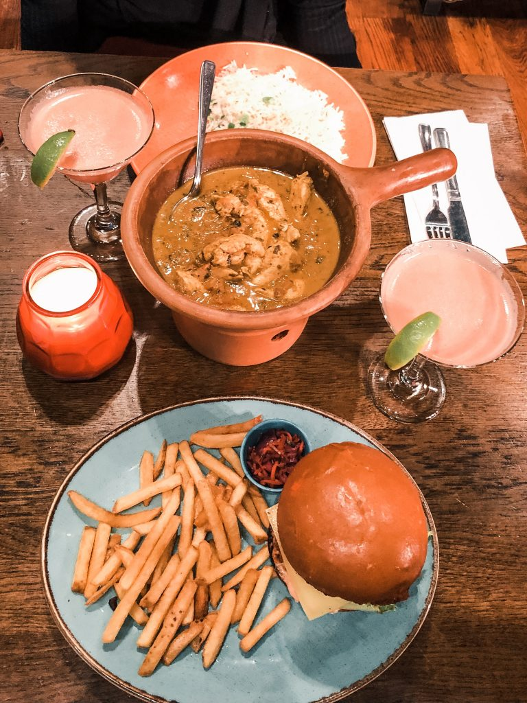 A photo of two mains, a burger and chips and a pot of Coconut Chicken Curry from Las Iguanas.