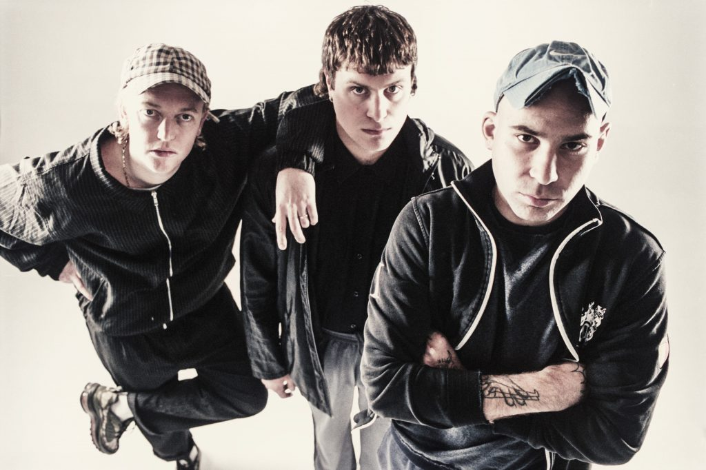 Three DMA's band members standing together, looking up at the camera, intimidatingly.