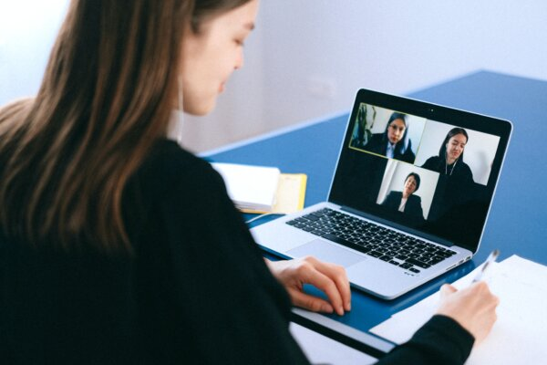A woman sat at a desk with three other women on her laptop screen on an online meeting. Looks like hybrid teaching.