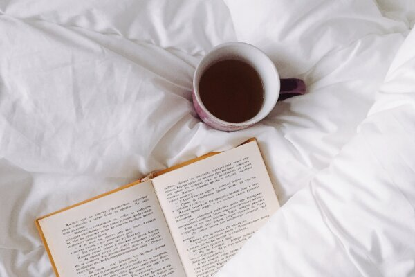 A book laid on crisp white bedding to represent the aesthetic of reading and the joy and comfort that can be found in books
