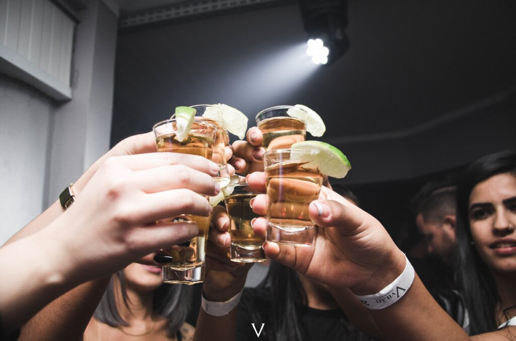 Shot glasses being clinked together by a group of people in a club. Young woman's face in shot.