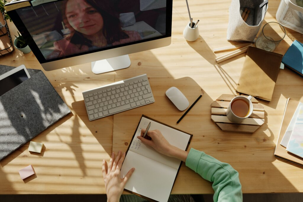 Person writing in notebook with a woman on the computer screen on an online meeting, possibly demonstrating hybrid teaching. Cluttered desk.