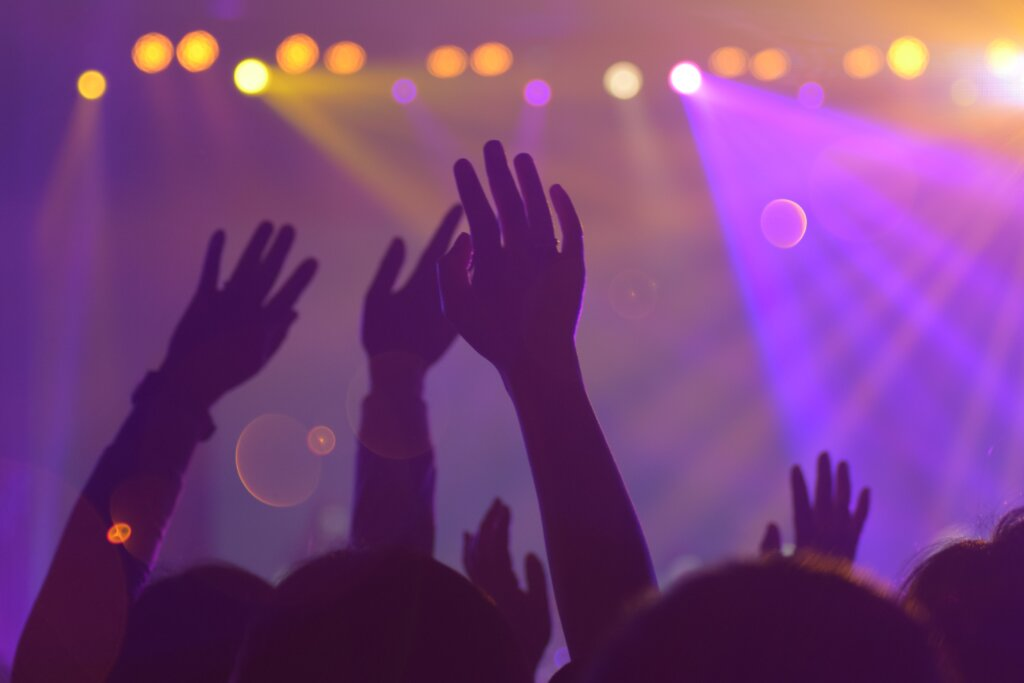 Hands up in a nightclub. Purple lighting.