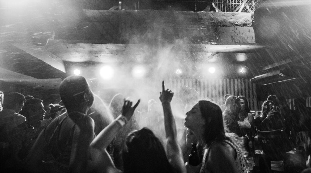 Black and white photo of people dancing in a club. Three young women in the forefront with one's arms up.