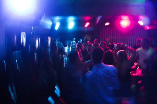 Blurry picture of people in a nightclub. Blue and pink lighting.